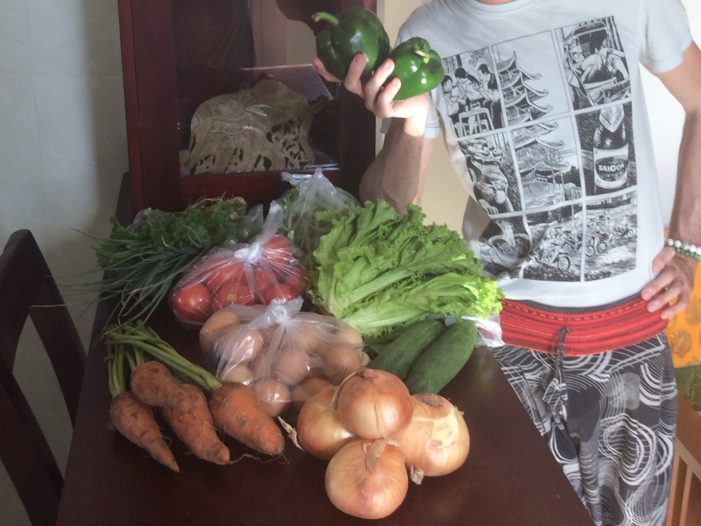 Curtiss poses with vegetables from the local outdoor market